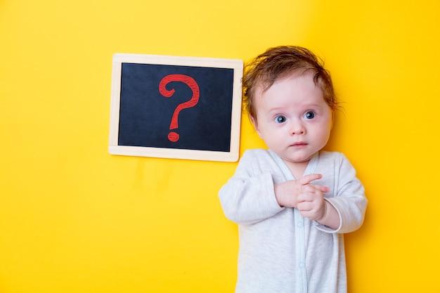 Małe dziecko z czarną tablicą i czerwonym pytaniem