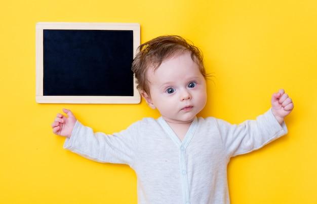 Małe dziecko z czarną tablicą