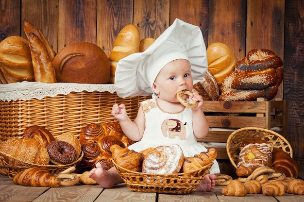 Małe dziecko z kapeluszem szefa kuchni i produktami piekarniczymi