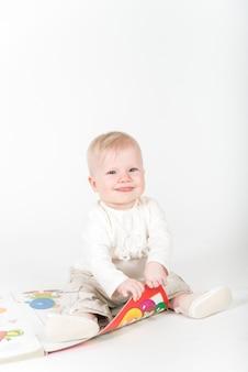 Małe dziecko z książką na białym