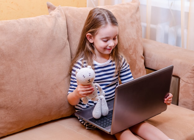 Małe dziecko z netbookiem i pluszakiem
