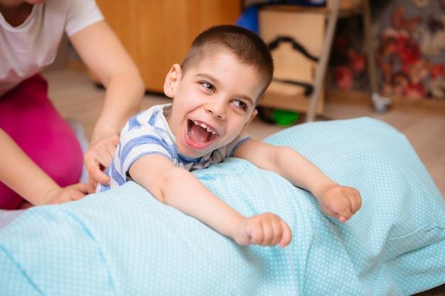 Małe dziecko z porażeniem mózgowym ma terapię mięśniowo-szkieletową, wykonując ćwiczenia