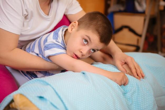 Małe dziecko z porażeniem mózgowym poddaje się terapii mięśniowo-szkieletowej, wykonując ćwiczenia związane z mocowaniem ciała