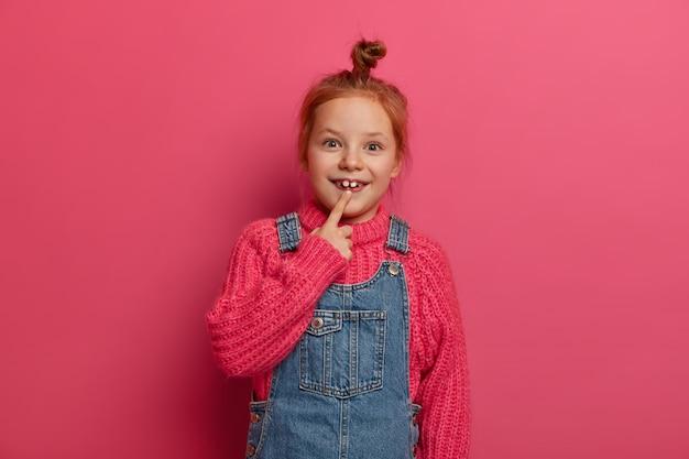 Małe dziecko z rudymi włosami wskazuje na dwa dorosłe zęby, ma radosny wyraz twarzy, nosi dzianinowy sweter i dżinsową sarafan, ma dobry nastrój, pozuje na różowej ścianie. koncepcja dzieciństwa