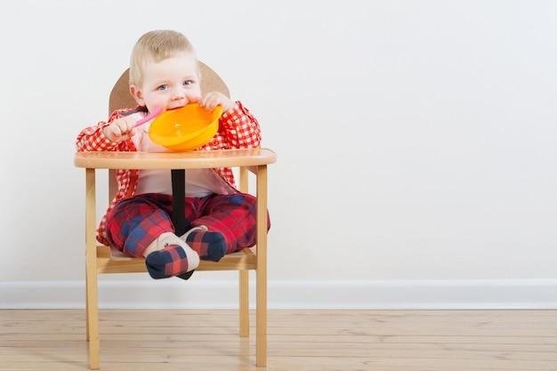 Małe dziecko z talerzem i łyżką na biel ścianie