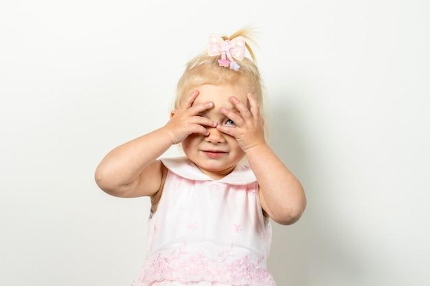 Małe dziecko zakrywa twarz rękami na jasnym tle.