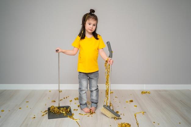 Małe dziecko żeńskie sprzątanie salonu z miotłą w domu. smutna dziewczyna trzyma miarkę i trzepaczkę. dziecko sprząta po sobie śmieci. mała dziewczynka sprząta dom po wakacjach.