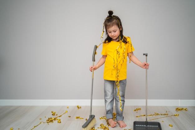 Małe dziecko żeńskie sprzątanie salonu z miotłą w domu. smutna dziewczyna trzyma miarkę i trzepaczkę.