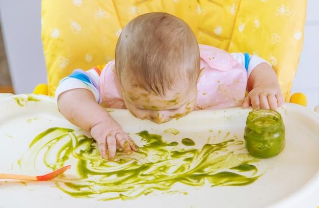 Małe dziecko zjada przecier z brokułów. selektywna ostrość. ludzie.