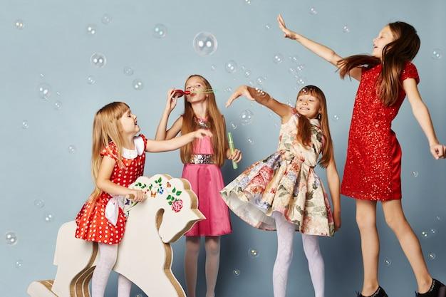 Małe dziewczynki bawią się i bawią, obchodzą urodziny, jedzą ciasta i dmuchają bańki. dziewczyny w pięknych sukienkach na niebieskim tle pozują i bawią się