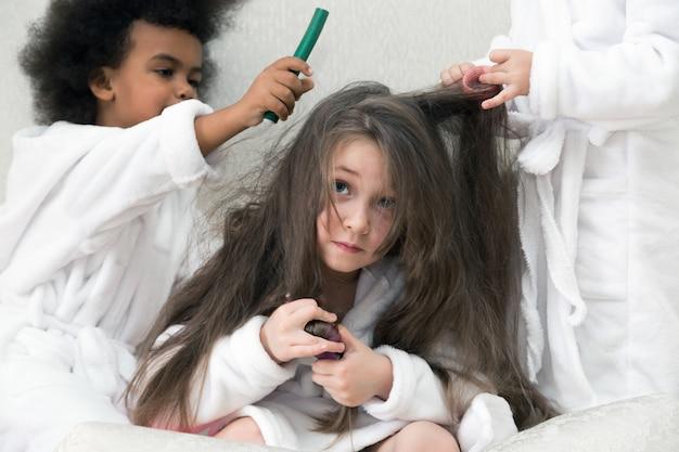 Małe dziewczynki bawią się lokówkami i spinkami do włosów.