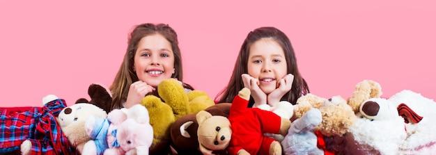 Małe dziewczynki bawią się misiami na różowym tle. dwie piękne szczęśliwe dziewczyny leżą i obejmują zabawki pluszowe w pokoju dzieci. dziewczyna przytulająca misie, dzieciństwo.