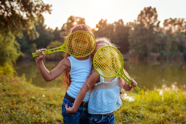 Małe dziewczynki bawią się na zewnątrz po grze w badmintona. siostry zakrywają twarze rakietami w letnim parku. dzieci .