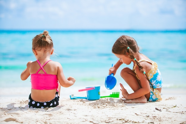 Małe dziewczynki bawiące się na tropikalnej plaży, grając razem i robiąc zamek z piasku