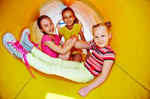 Małe dziewczynki bawiące się na zjeżdżalni na placu zabaw