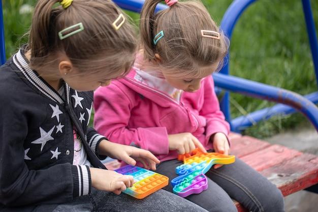 Małe dziewczynki bawiące się nową zabawką typu fidget popularną wśród dzieci pomagają im się skoncentrować