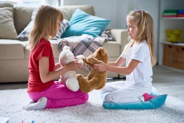 Małe dziewczynki bawiące się pluszowymi zabawkami