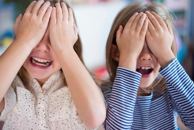 Małe dziewczynki bawiące się w chowanego