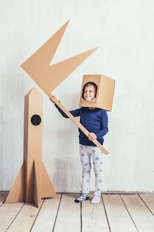 Małe dziewczynki bawiące się w kosmonautę z tekturową rakietą i tekturowym hełmem