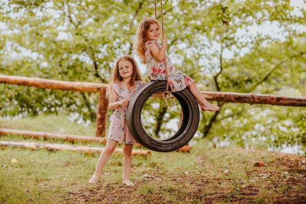 Małe dziewczynki bawić się huśtawką koła