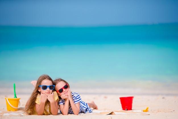 Małe dziewczynki bawić się plażowymi zabawkami podczas tropikalnego wakacje