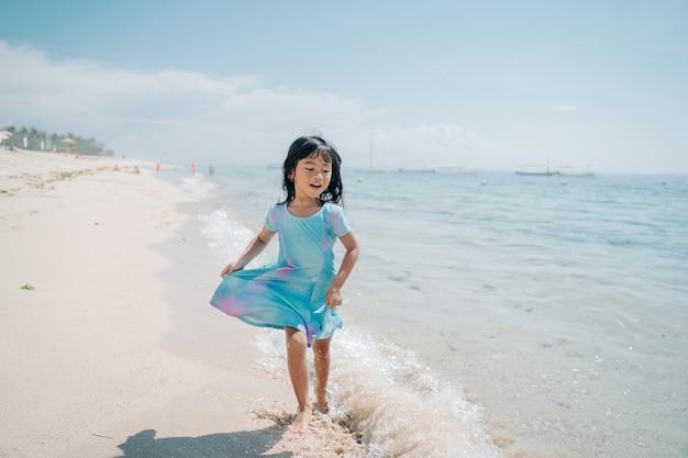 Małe dziewczynki biegają i śmieją się na plaży
