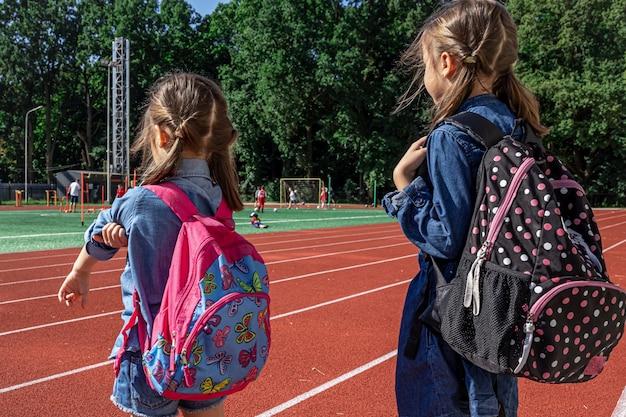Małe dziewczynki dzieci w wieku szkolnym z plecakami na stadionie, obserwujące chłopców grających w piłkę nożną.