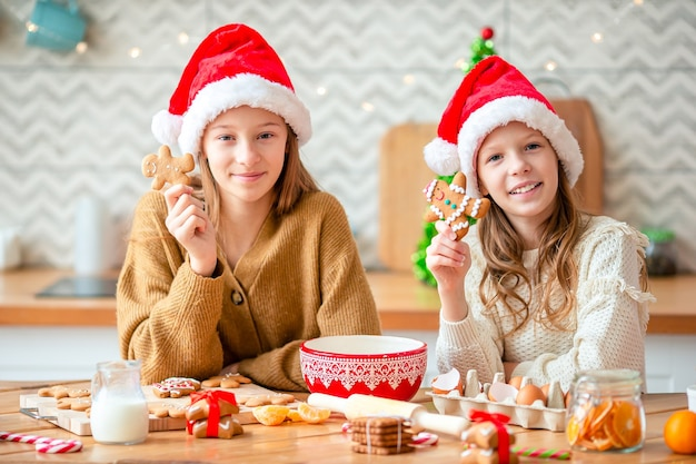 Małe dziewczynki gotują świąteczne pierniki