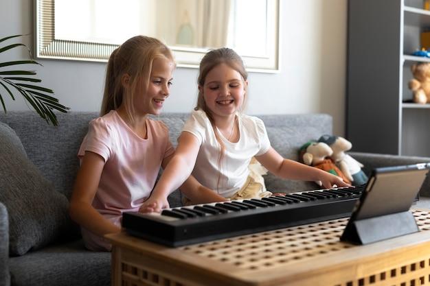 Małe dziewczynki grają na klawiaturze w domu