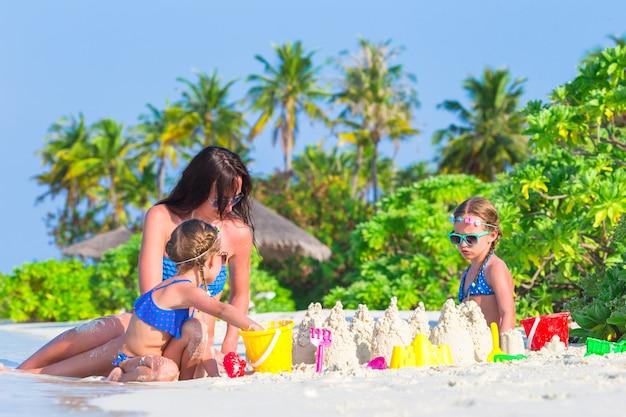 Małe dziewczynki i szczęśliwa matka bawić się zabawkami plażowymi na wakacjach