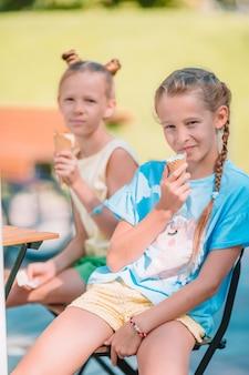 Małe dziewczynki je lody outdoors przy latem w plenerowej kawiarni