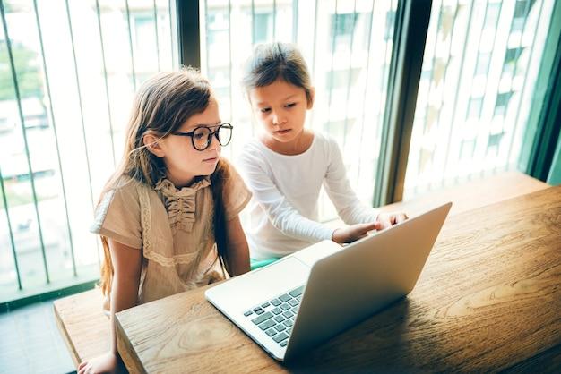 Małe dziewczynki korzystające z koncepcji komputera