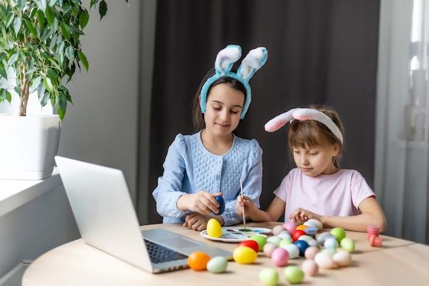 Małe dziewczynki malowanie pisanek z laptopem.
