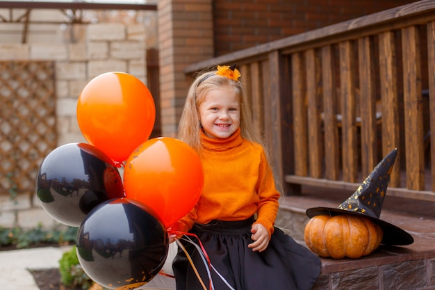 Małe dziewczynki na progu domu w kostiumach na halloween