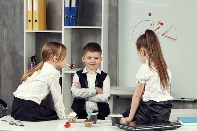 Małe dziewczynki na zdjęciach pracowników biurowych siedzą na stole i rozmawiają.