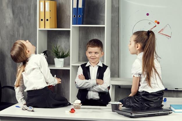 Małe dziewczynki na zdjęciach pracowników biurowych siedzą na stole i śmieją się ze swojego małego szefa