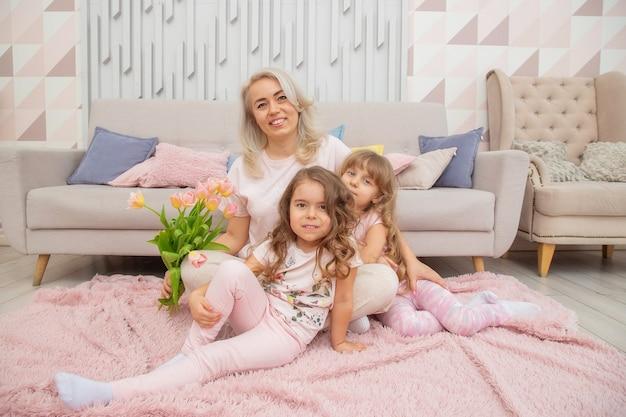 Małe dziewczynki o kaukaskim wyglądzie przytulają się z matką, siedząc na podłodze przed sofą w jasnym salonie w stylu skandynawskim