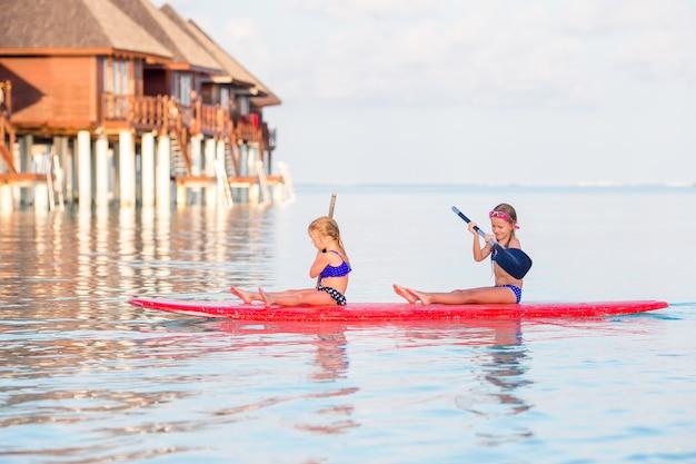Małe dziewczynki pływa na desce surfingowej podczas wakacji