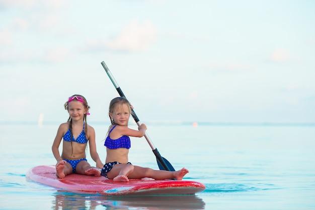 Małe dziewczynki pływa na surfboard podczas wakacje