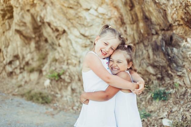 Małe dziewczynki przytulanie na zewnątrz