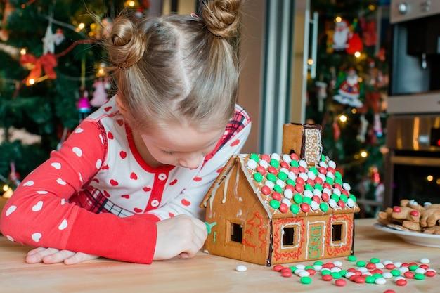 Małe dziewczynki robią bożenarodzeniowego piernikowego dom przy kominkiem w dekorującym żywym pokoju.