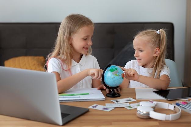 Małe dziewczynki robią razem szkołę online w domu
