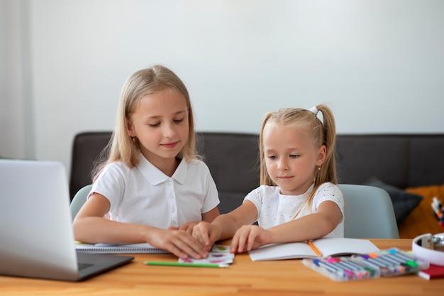 Małe dziewczynki robią razem szkołę online