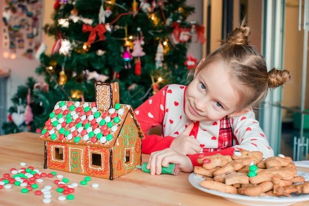Małe dziewczynki robiące świąteczny dom z piernika przy kominku w urządzonym salonie.