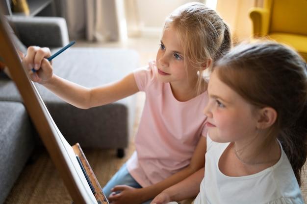 Małe dziewczynki rysują razem w domu na sztalugach