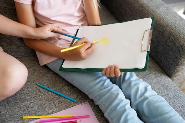 Małe dziewczynki rysują razem w domu