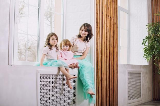 Małe dziewczynki są piękne, urocze i zabawne, a ich mama w spódnicach siedzi na oknie