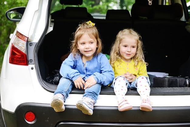 Małe dziewczynki siedzące w samochodzie