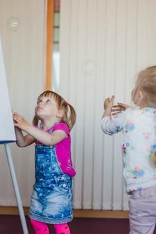 Małe dziewczynki stojących gapi się na pęcherzyków mydlanych