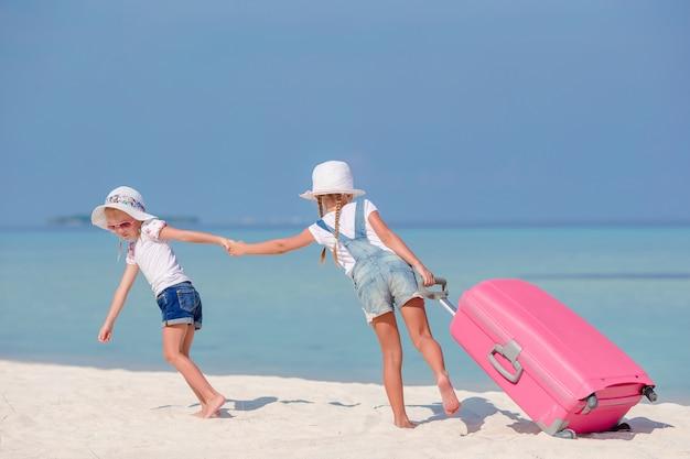 Małe dziewczynki turystów z dużą walizką na tropikalnej plaży biały